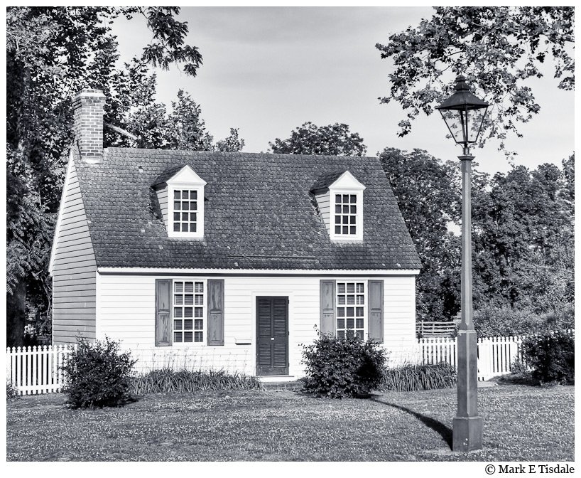 Black and white photo of a house with a White Picket Fence - Williamsburg, Virginia
